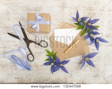 Gift box blue flowers scissors pencil satin ribbon and envelope with greeting card on the wooden painted board
