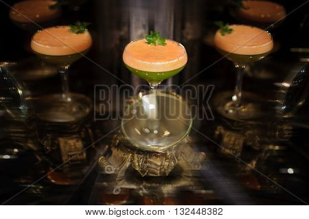 Colorfull orange and green cocktail with mint with reflection