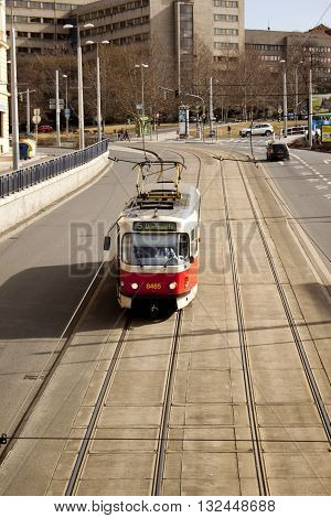 The tram moves along the rails, Prague street on a sunny day