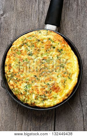 Omelette in frying pan on wooden background top view