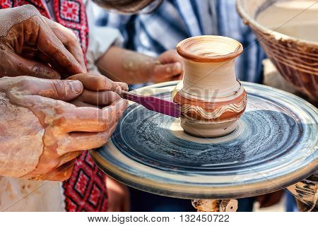 Hands working on pottery wheel. Sculptor, Potter. Human Hands creating a new ceramic pot.