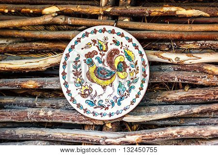 Ukrainian handmade earthenware utensil. Painted plate on wooden wall. Souvenirs From Ukraine in ethnic style. Decorative plate.