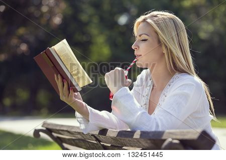 Portrait of a beautiful young woman drinking juice and reading a book on a sunny day in the park