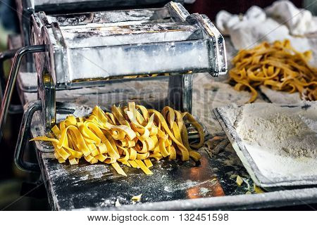 Fresh pasta and pasta machine on kitchen table. Fettuccine homemade. Process of making homemade pasta linguine, closeup.