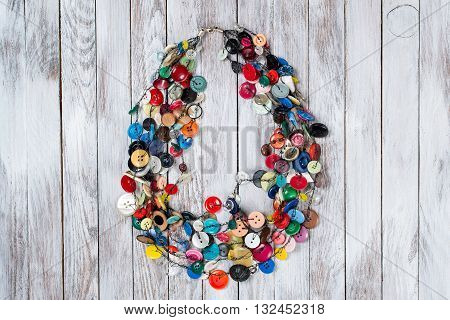 Handmade bright colored jewelry made of plastic buttons on the white wooden background.