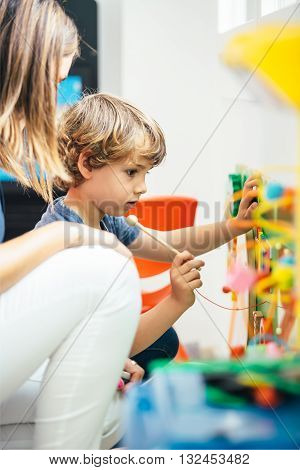 Side view of cute boy playing xylophone with mother sitting near