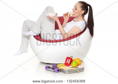 Young beautiful woman with donuts sits on an armchair. Concept of healthy lifestyle.