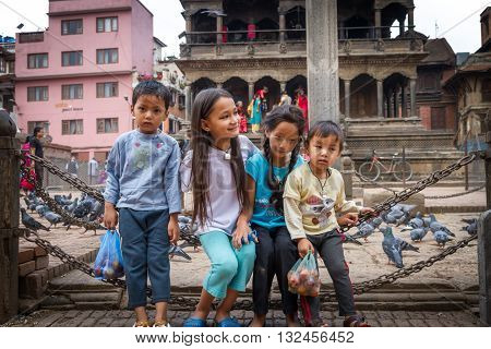 KathmanduNepal - March 26 2016: Smiling cute Nepali childs playing on the Iron chains are feeling shy to pose for photographs.