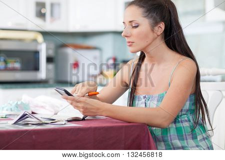 The young pregnant woman plans the family budget on the house kitchen.