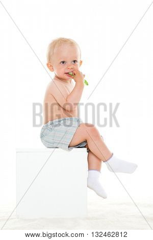 Small child playing with a new toothbrush on a white background. Concept of healthy  clean teeth.