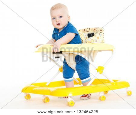 The small child learns to walk by means of Baby walker on a white background.
