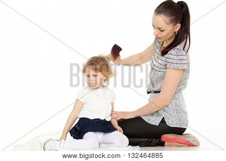 Young mother brushing hair of the small daughter on a white background.