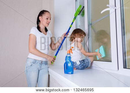 Happy young mother and little daughter cleaning windows in the house.