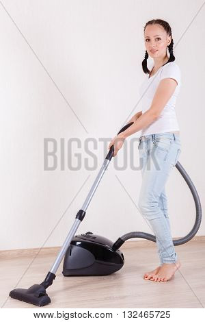Young woman cleans the floor at home with a vacuum cleaner. Housekeeping.