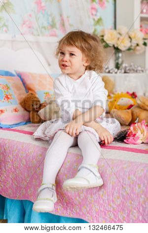 Little girl combing hair sits on the bed in children room. 2 year old.
