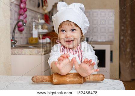Little girl in apron and cap of the cook with rolling pin sits at the dining table in the kitchen in the house. Mother's helper. 2 year old.