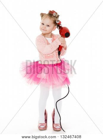 Cute little girl with curlers on her head dressed in pink clothes and a huge mother's shoes holds a hair dryer on a white background. Little fashionista.  3 year old.