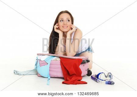 Young happy woman with suitcase sits on a white background. Vacation.