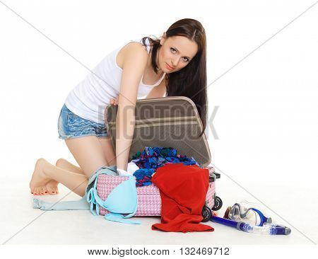 Young unhappy woman with suitcase sits on a white background. Vacation.