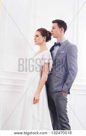 Attractive bride in white dress and handsome groom in grey tuxedo posing in retro interior.