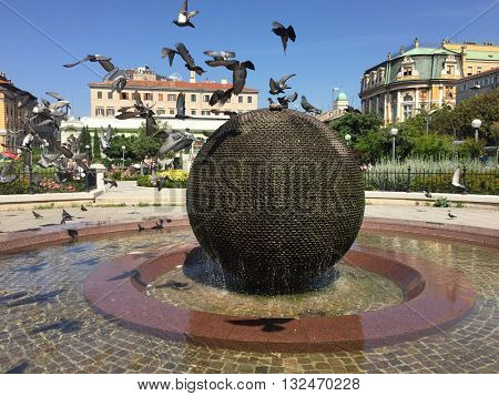 RIJEKA, CROATIA - MAY 27th, 2016: Fountain in front of National Theatre Ivan Zajc with flock of pigeons in flight, in Rijeka, Croatia. Sphere fountain was made by famous Croatian artist Dusan Dzamonja