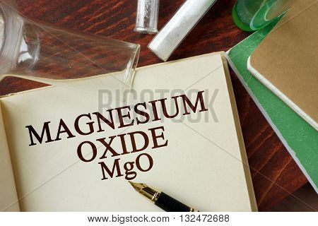 Word magnesium oxide written on a page. Chemistry concept.