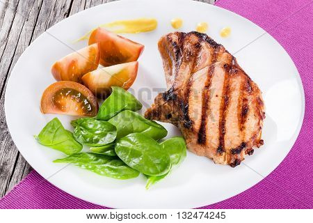 grilled pork chops on a white dish with slices of black tomatoes spinach leaves and mustard on a table mat close-up