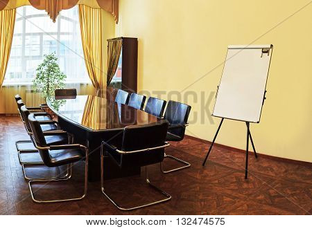Modern interior of empty conference room with window flipchart and wooden table