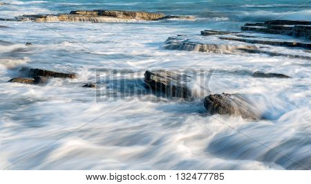 Sea waves crashing on plates of sea rocks creating small waterfalls and smooth streams of water.