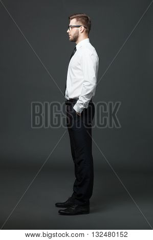 Fullbody Profile View Of Handsome Businessman On Dark Gray Background.