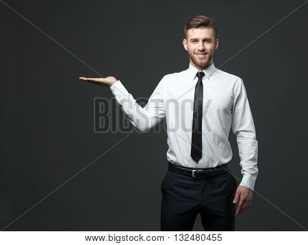 Handsome Young Businessman Holding His Arm Up Presenting Copyspace.