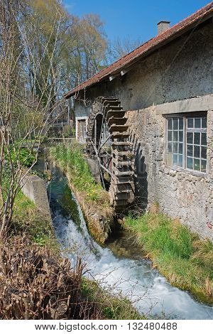 historic water wheel at work in a little creek