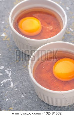 Raw eggs with tomatoes in the ramekins on the stone table vertical