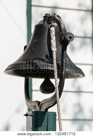 Dinner Bell hangs on green post with white rope