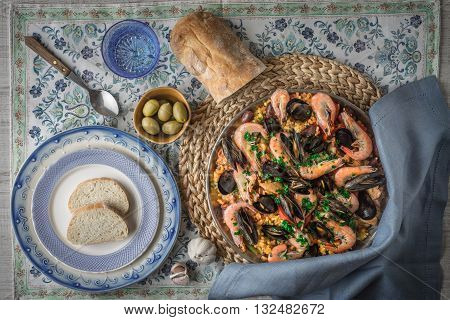 Paella on the metal plate on the beautiful napkin with tableware and bread top view
