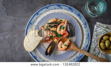 Plate with paella on the dark stone table with different accessories top view
