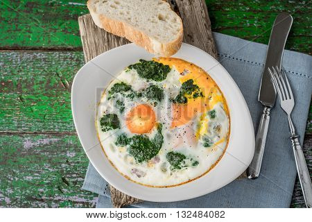 Florentine eggs with pureed spinach on the old wooden board