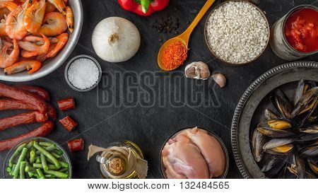 Ingredients for paella on the dark stone table horizontal