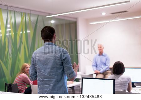 student answering a question in classroom, mature teacher and students in computer lab classroom
