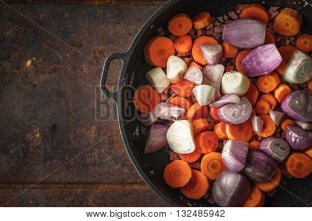 Shallot and carrots in the pan on the metal background