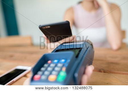 Female pay on mobile phone with pos terminal