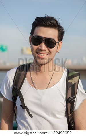close up face of younger asian man wearing sun glasses standing outdoor