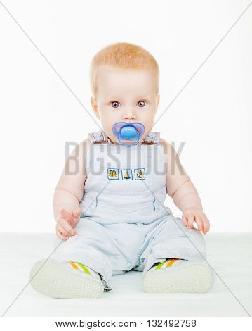 Lovely baby sitting on the floor with a pacifier isolated on white background
