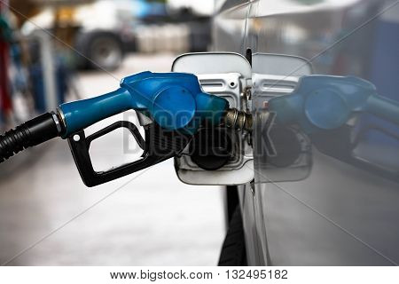 nozzle fill fuel into tank  in gas station