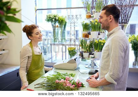 people, shopping, sale, floristry and consumerism concept - happy smiling florist woman and man or customer talking at flower shop