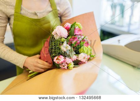 people, business, sale and floristry concept - close up of florist woman wrapping bunch into paper at flower shop