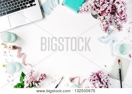 Workspace with paintbrush laptop lilac flowers bouquet spool with beige and blue ribbon mint diary on white background. Flat lay top view
