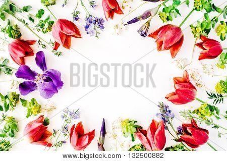 floral frame with red tulips yellow flowers purple iris branches leaves and petals isolated on white background. flat lay overhead view
