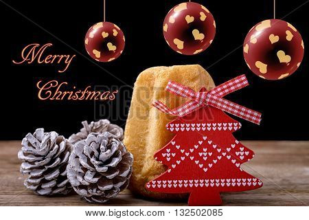 pandoro cake with pine cone and red wooden christmas tree on wood and christmas balls and merry christmas written on black background