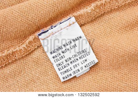 Washing instructions label on yellow cloth as a background
